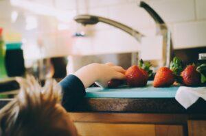 child reaching for fresh strawberries